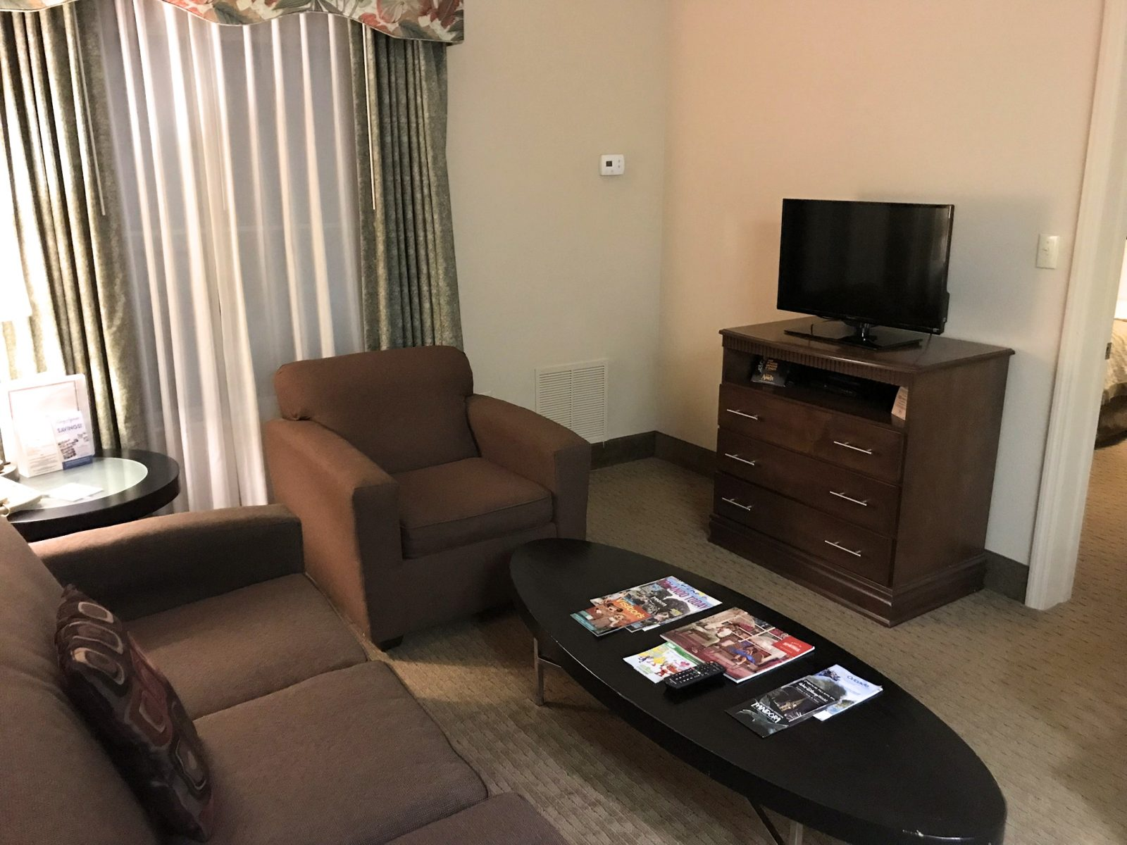 sitting area in the room, brown couches, black tables and tv