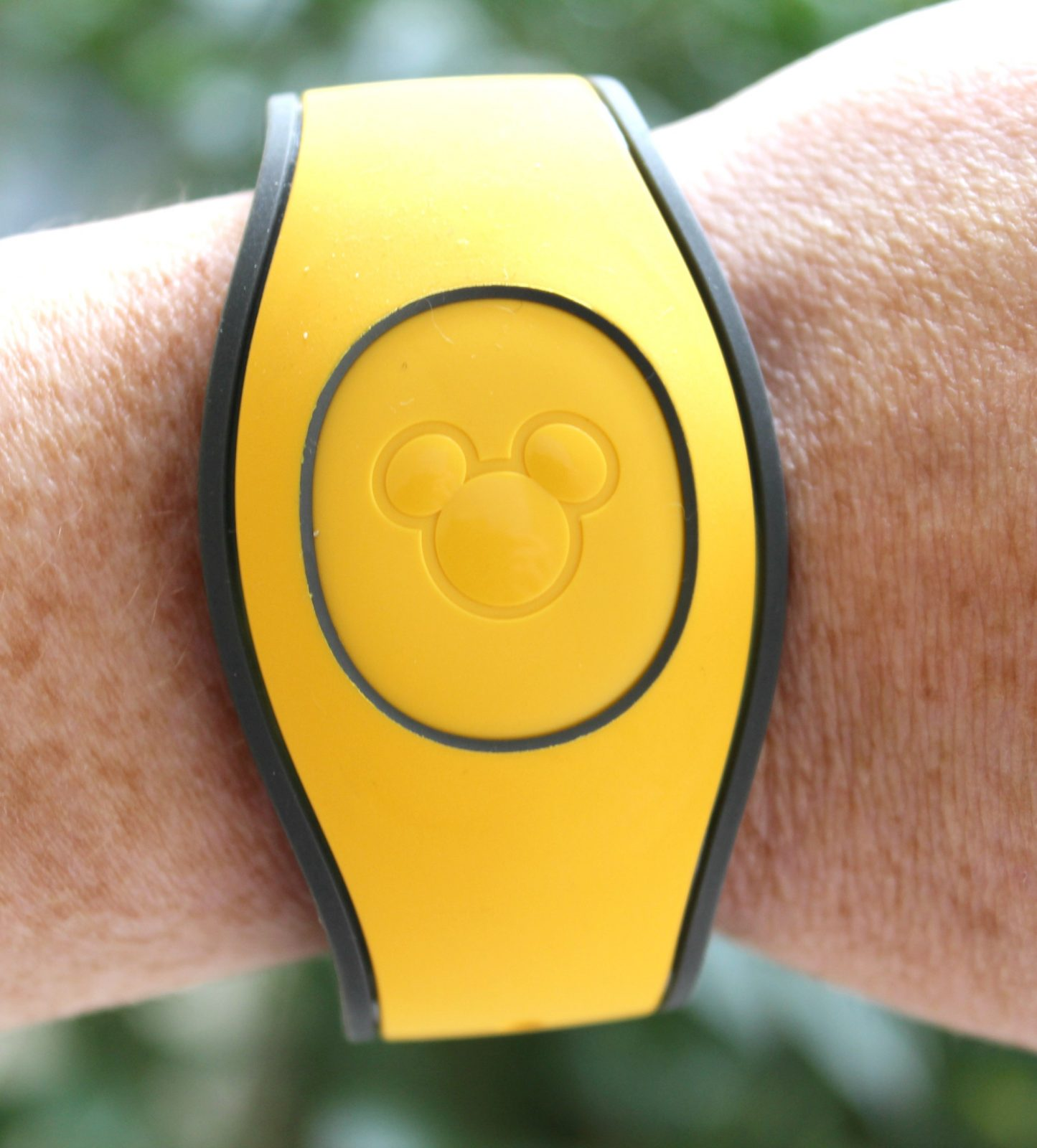 yellow disney magic band on a wrist