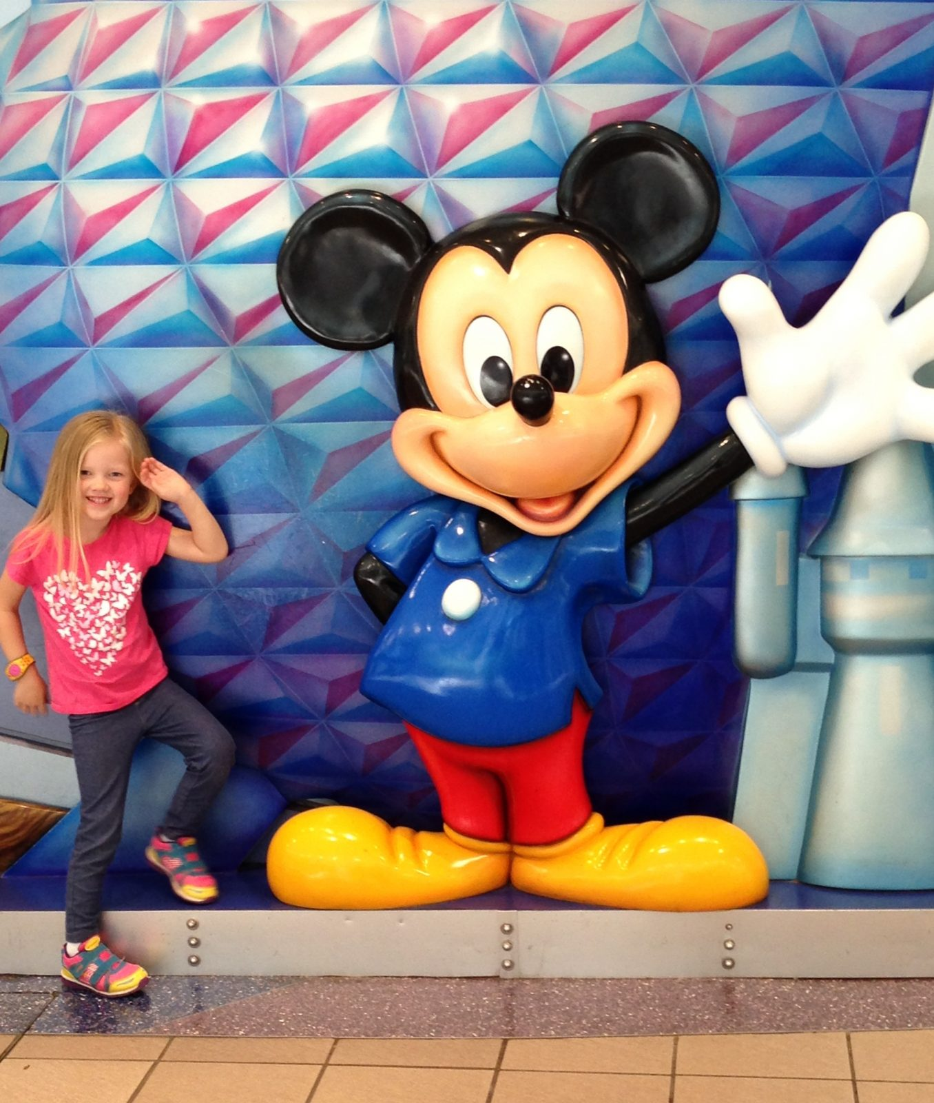 Little girl posing next to mickey statue
