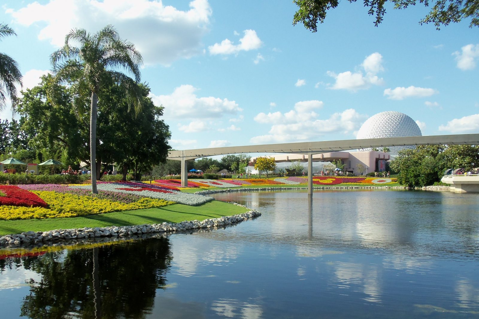 view outside of epcot, colorful flowers, water way, monorail track, and the iconic spaceship earth ride in Epcot