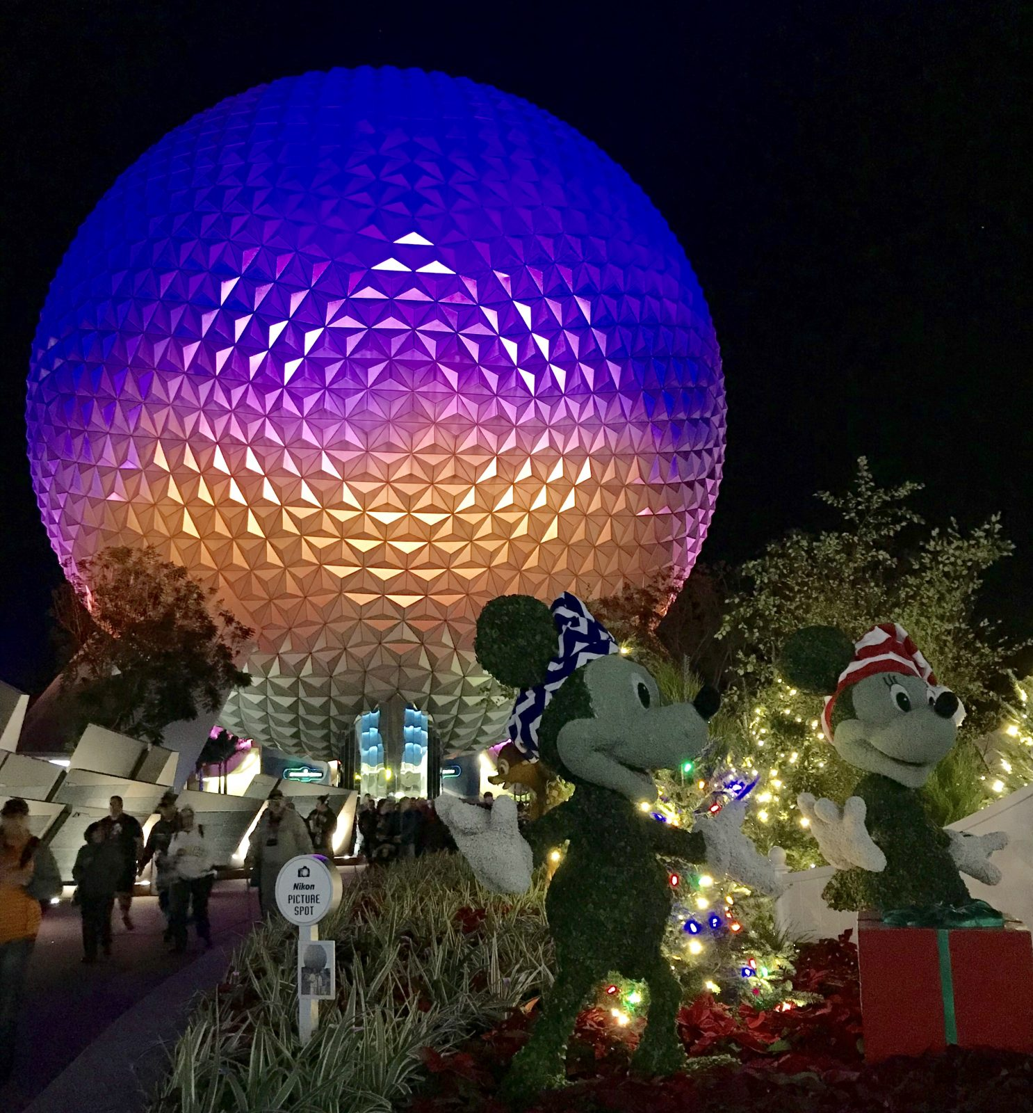 epcot's spaceship earth geosphere at night with mickey and minnie statues in the foreground