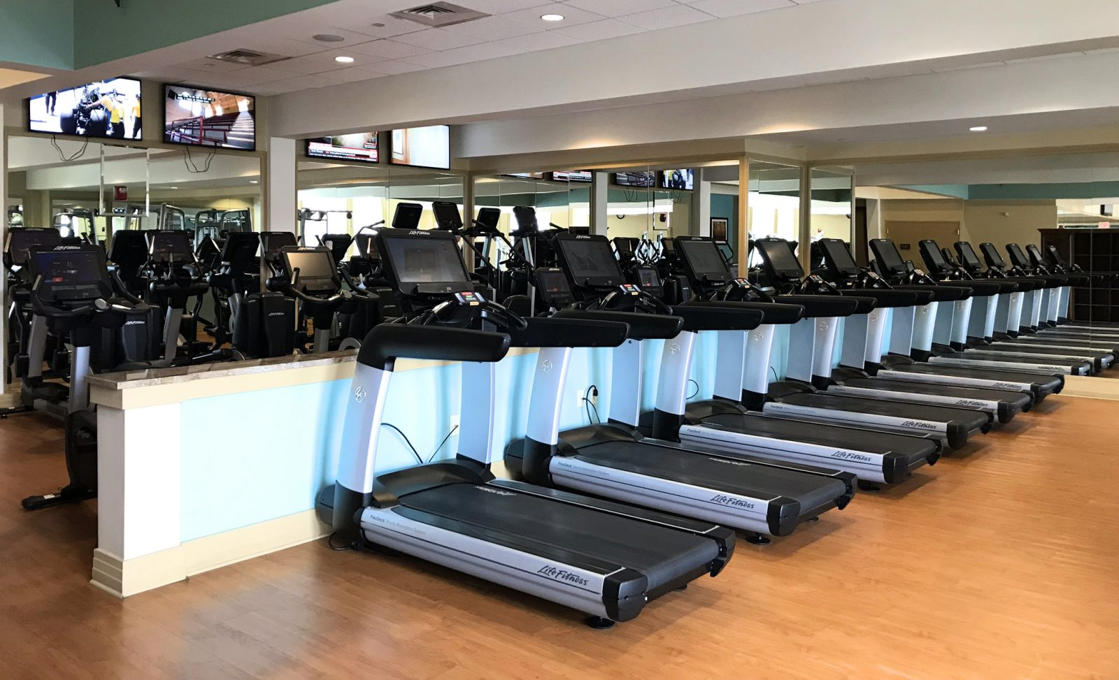 resort fitness center with cardio machines and televisions