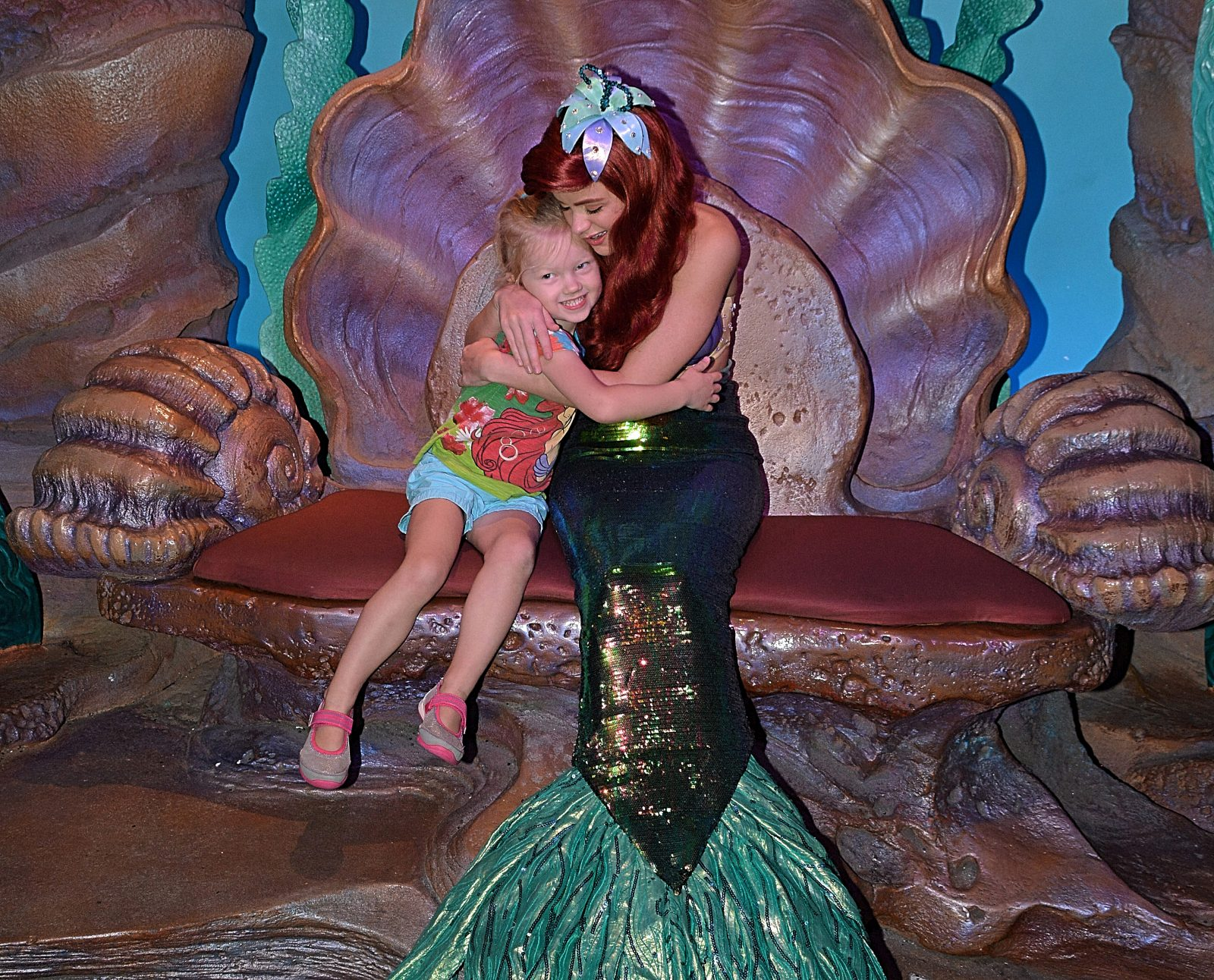 little girl hugging disney character ariel in ariel's grotto