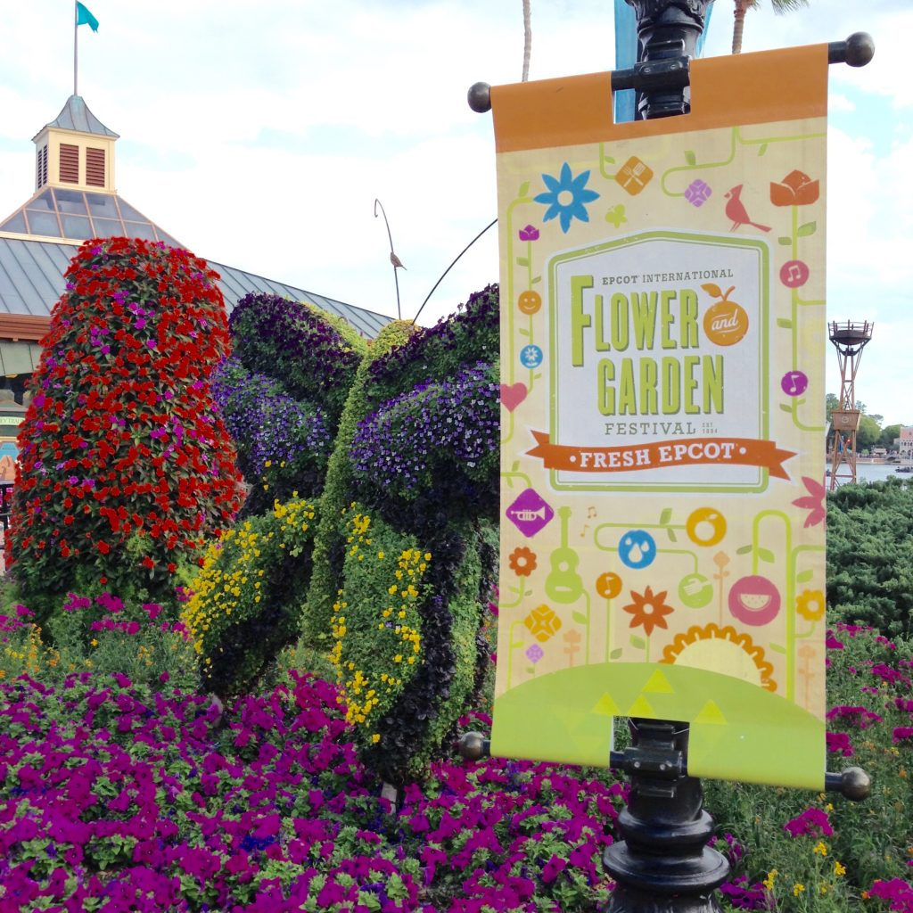 flower and garden festival sign in front of a a butterfly made out of plants and flowers