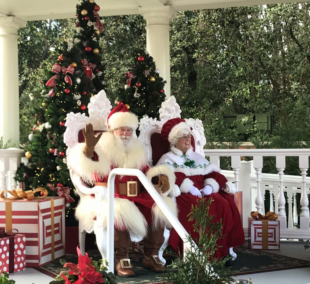 santa and mrs. claus sitting under a pavilion with a tree and presents behind them