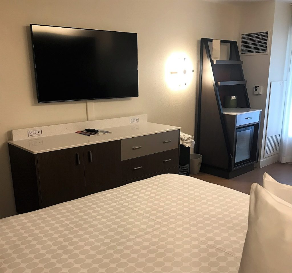 Bed, TV and storage in an All Star Movies Resort refurbished room