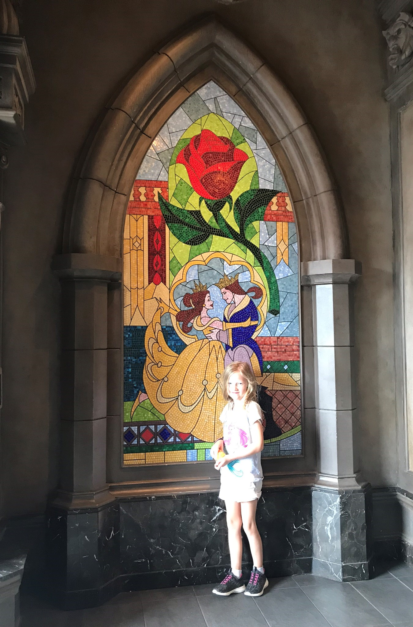 little girl standing in front of the beauty and the beast stained glass window