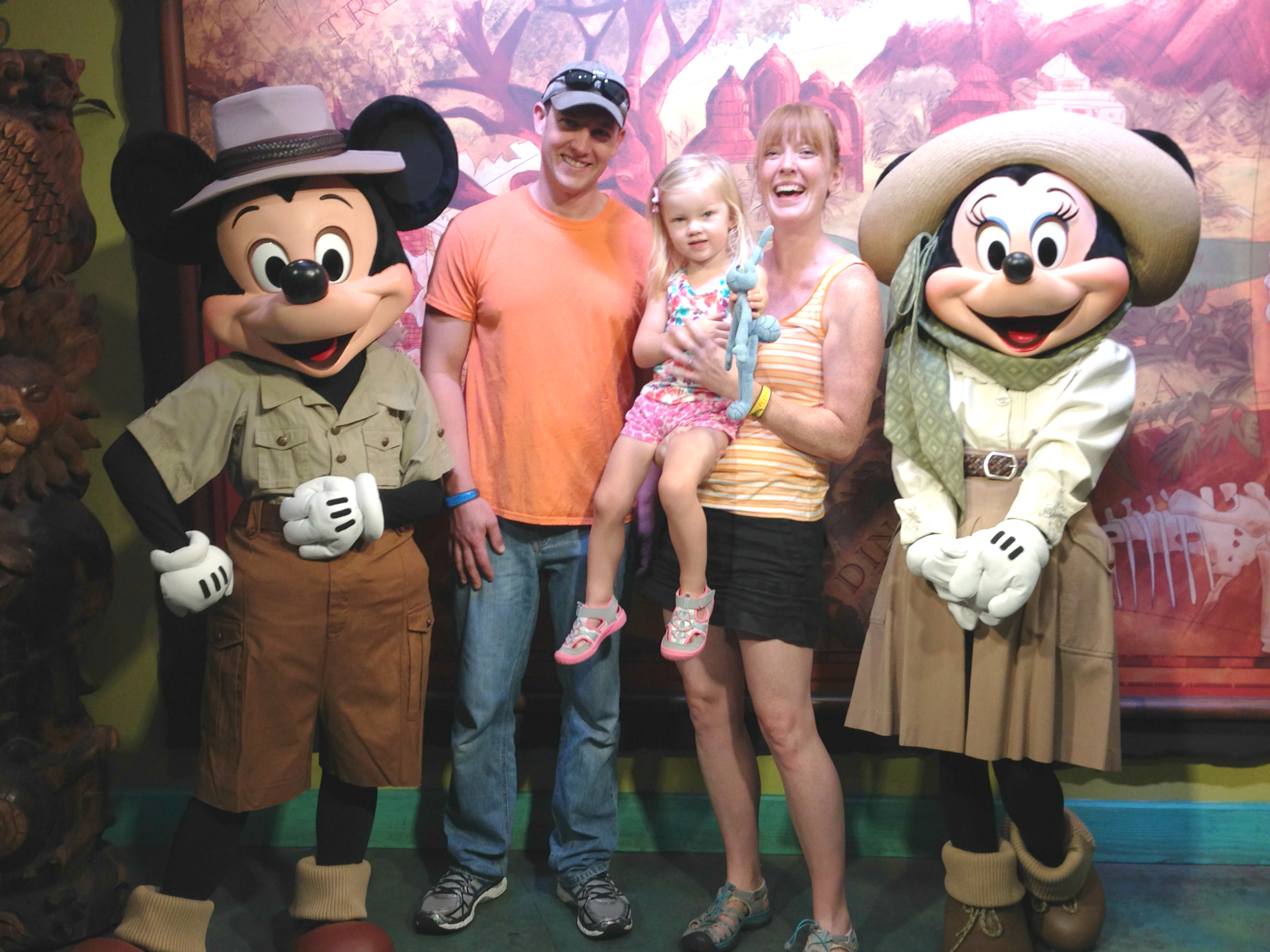 family posing with disney characters mickey and minnie in safari outfits