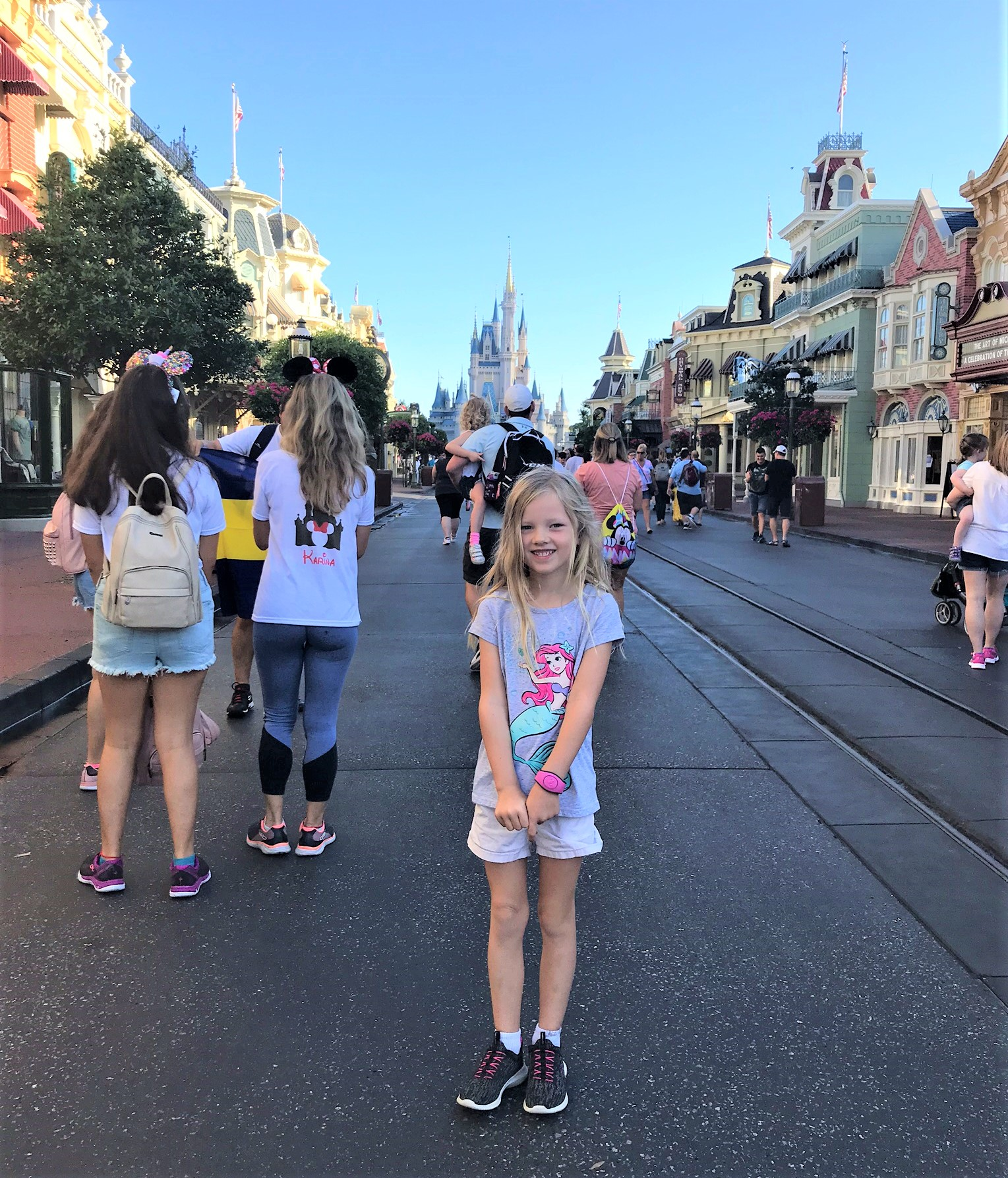 little girl on main street with cinderella's castle in the background