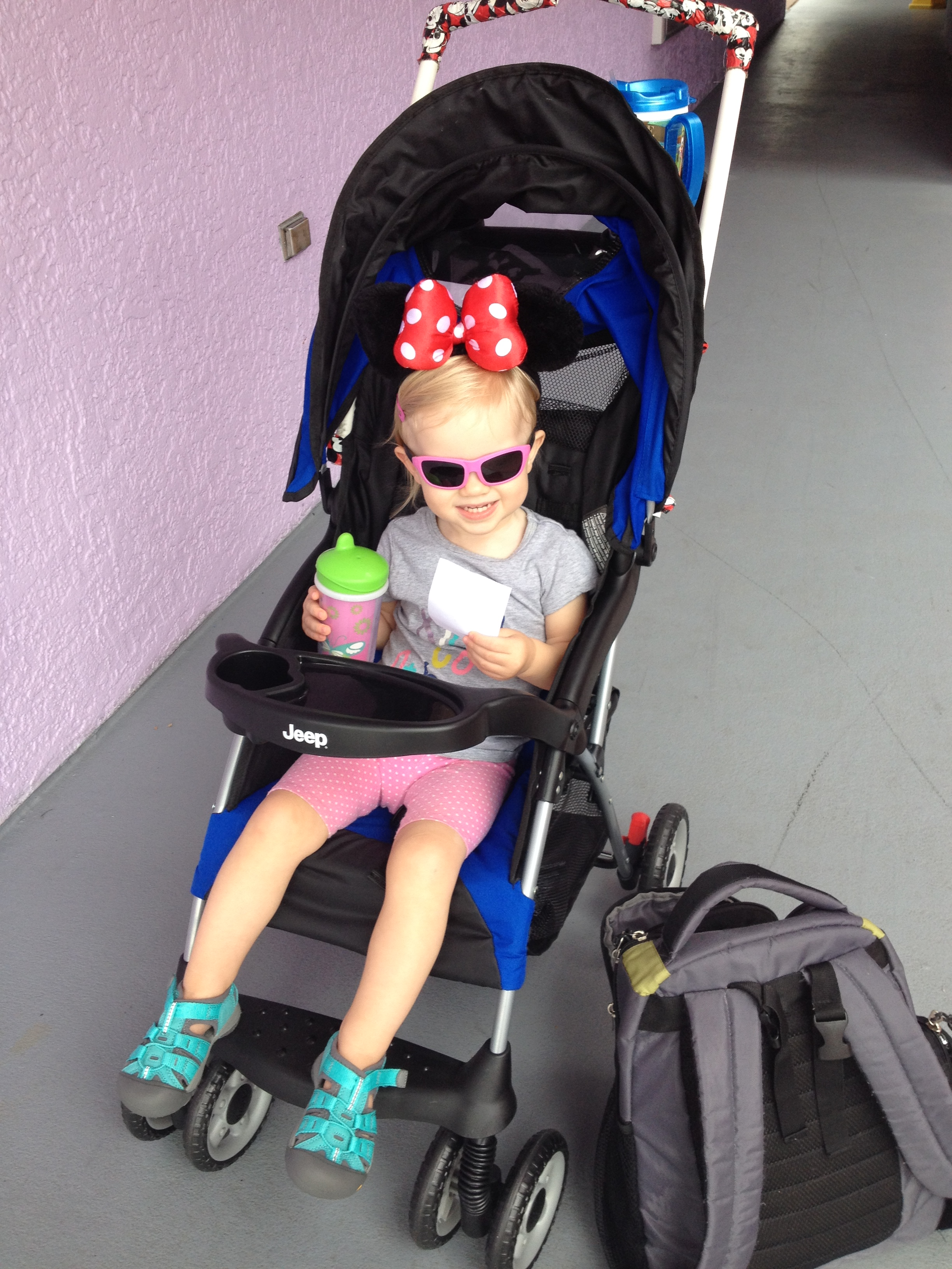 little girl sitting in a stroller with minnie mouse ears