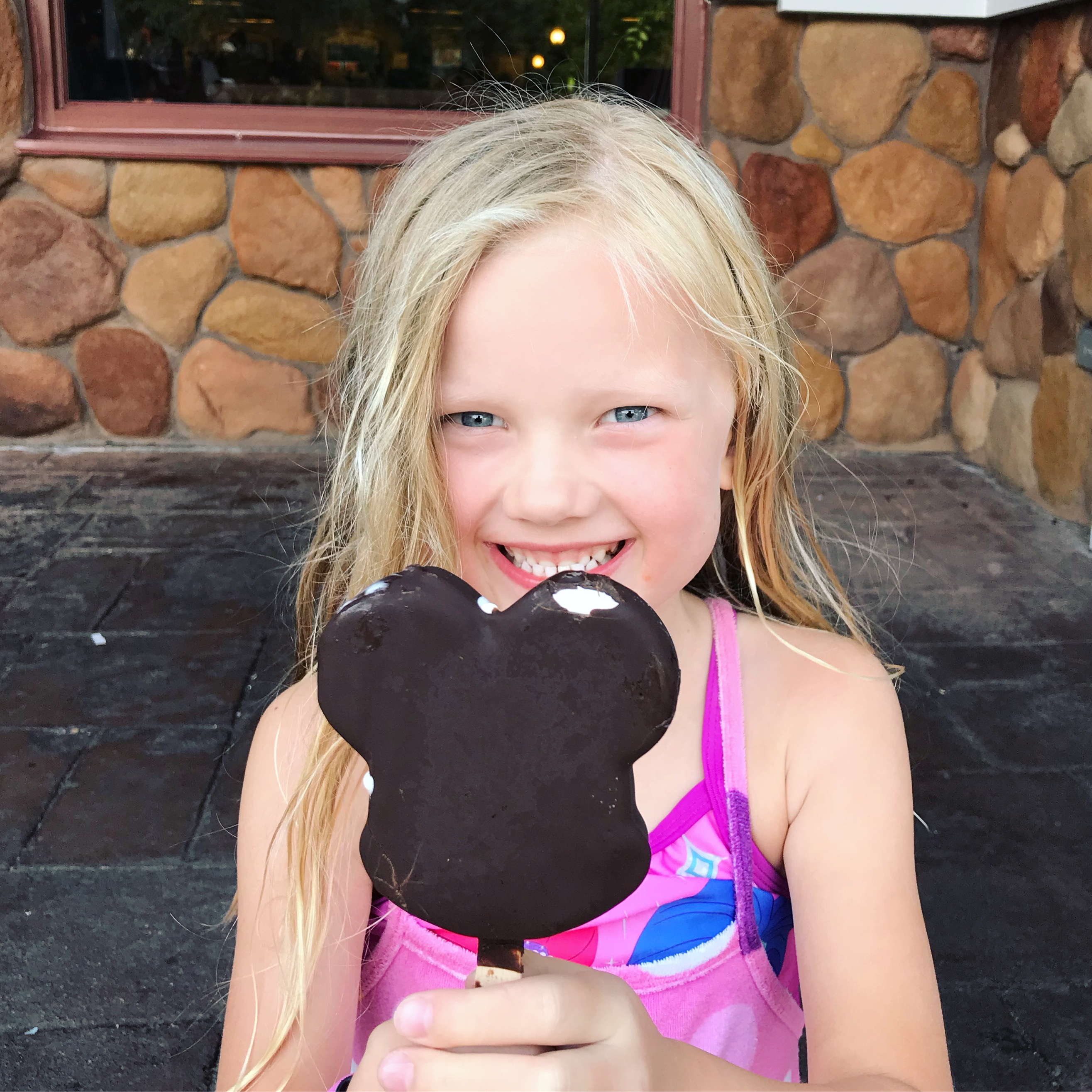 little girl enjoying a chocolate dipped mickey ice cream