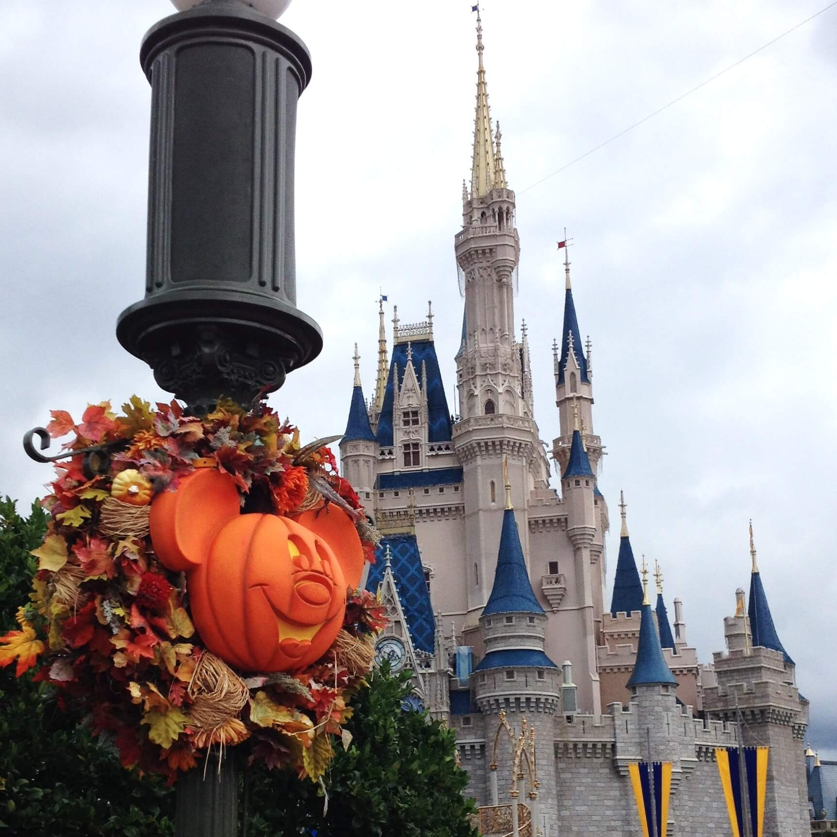 fall wreath with mickey mouse pumpkin in front of cinderella's castle