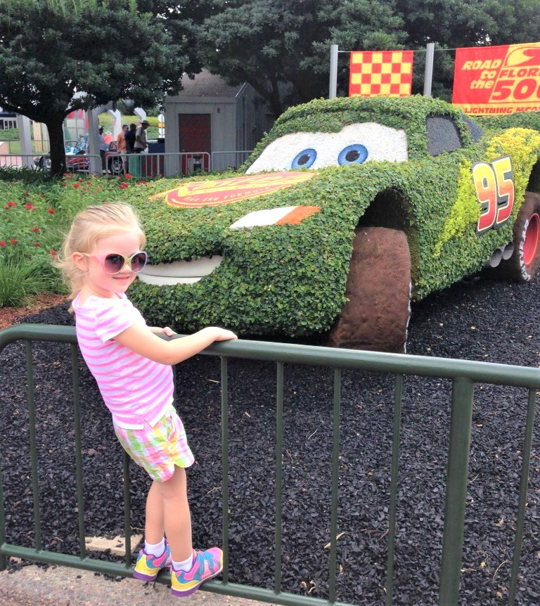 girl in front of bush shaped like lightning mcqueen