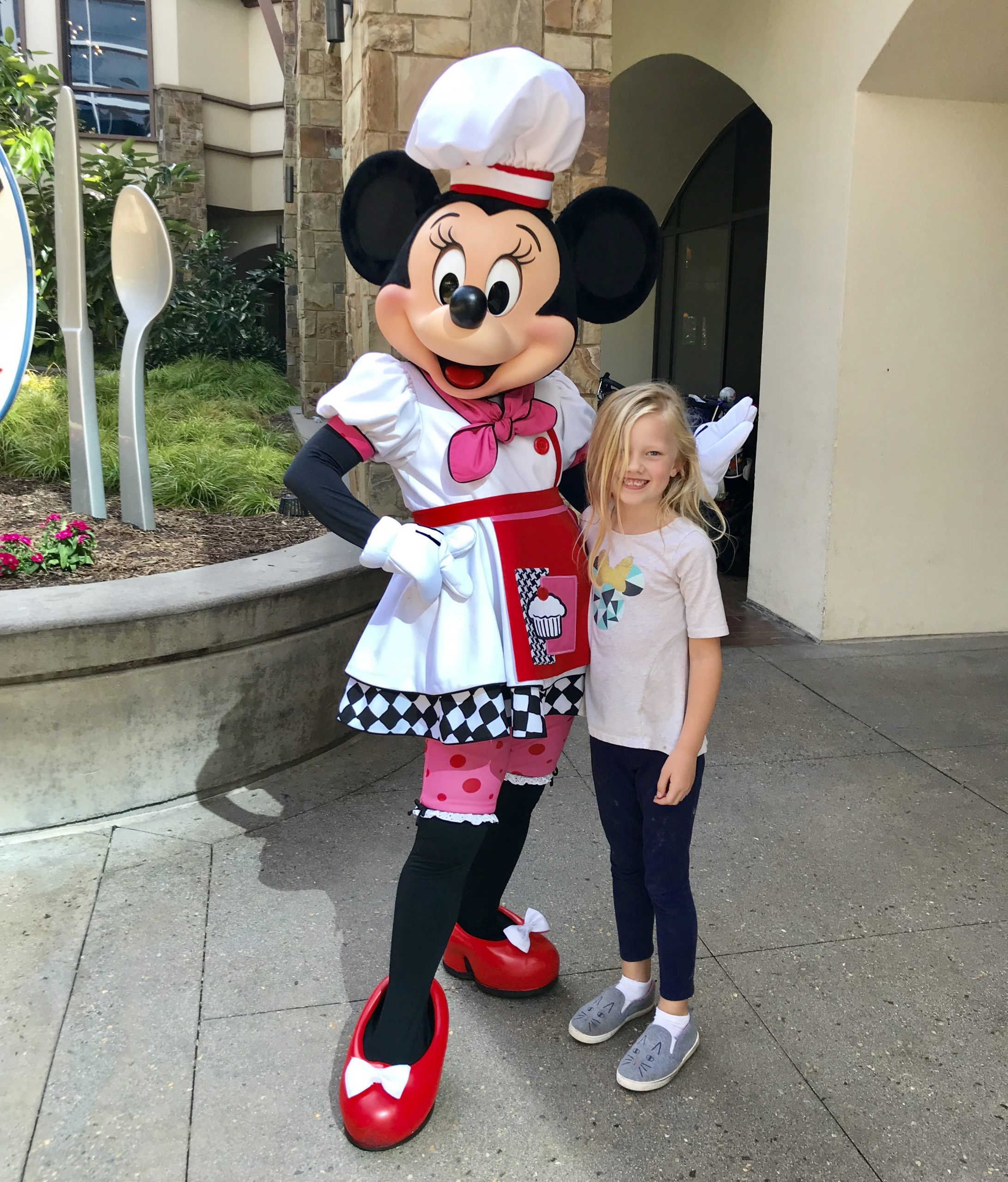 little girl posing with chef minnie mouse