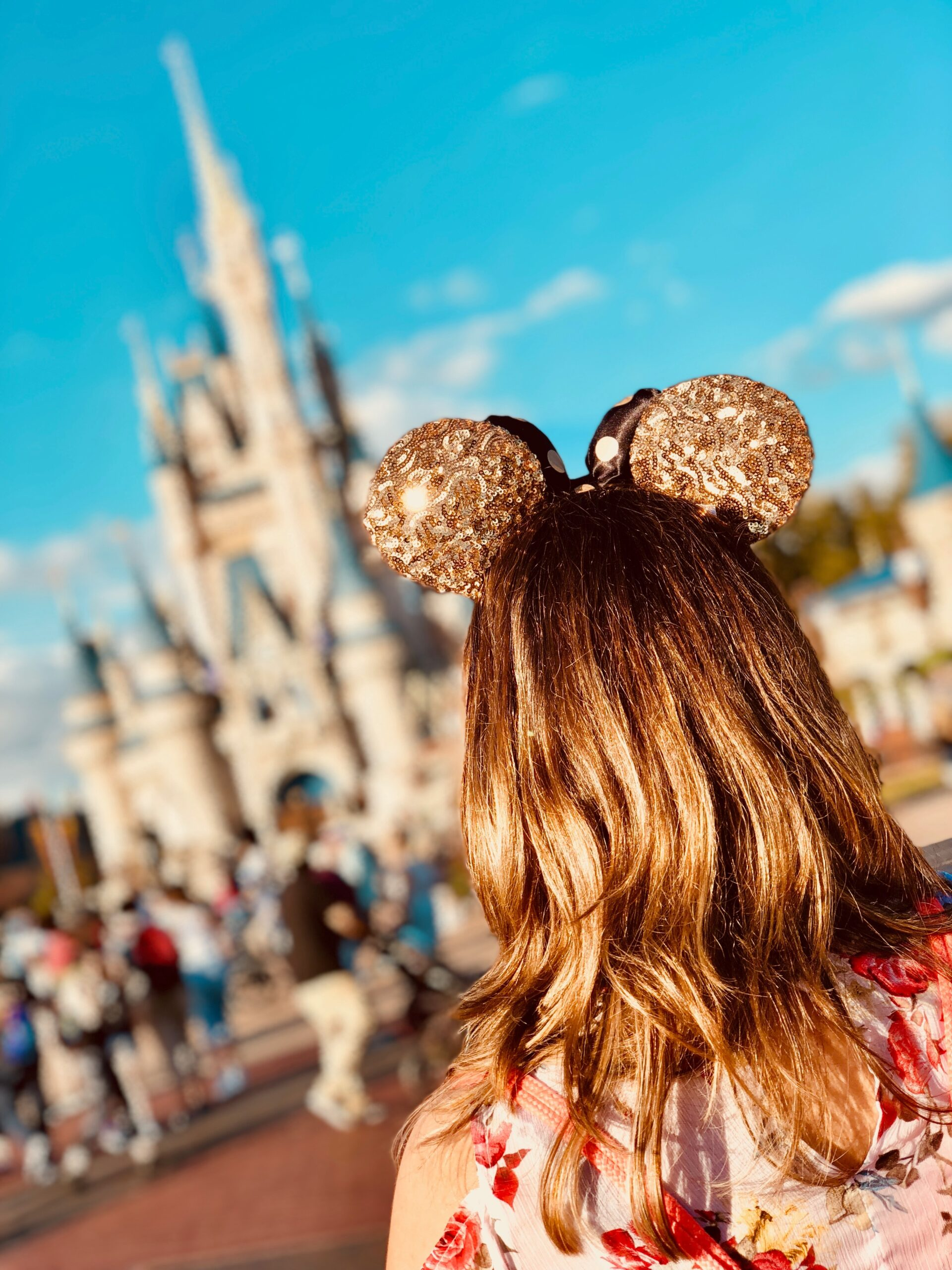 woman with mickey ears looking a cinderella castle